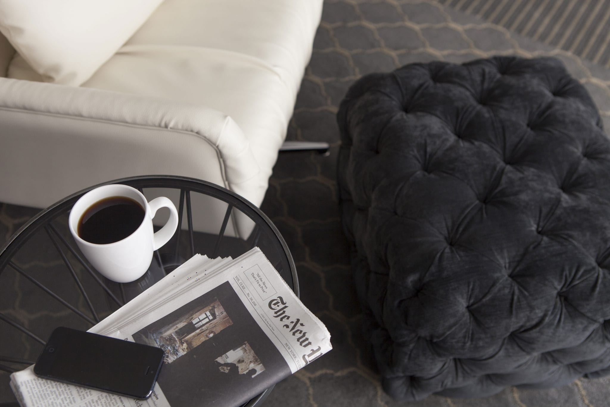 Coffee and a newspaper sit on the table next to a white couch.