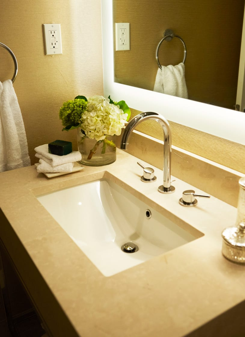 Warmly lit bathroom of an Affinia Hotel guestroom. the wide rectangle sink has a gooseneck water faucet. To the left is a large round vessel holding flowers, with a stack of face towels just in front of it.