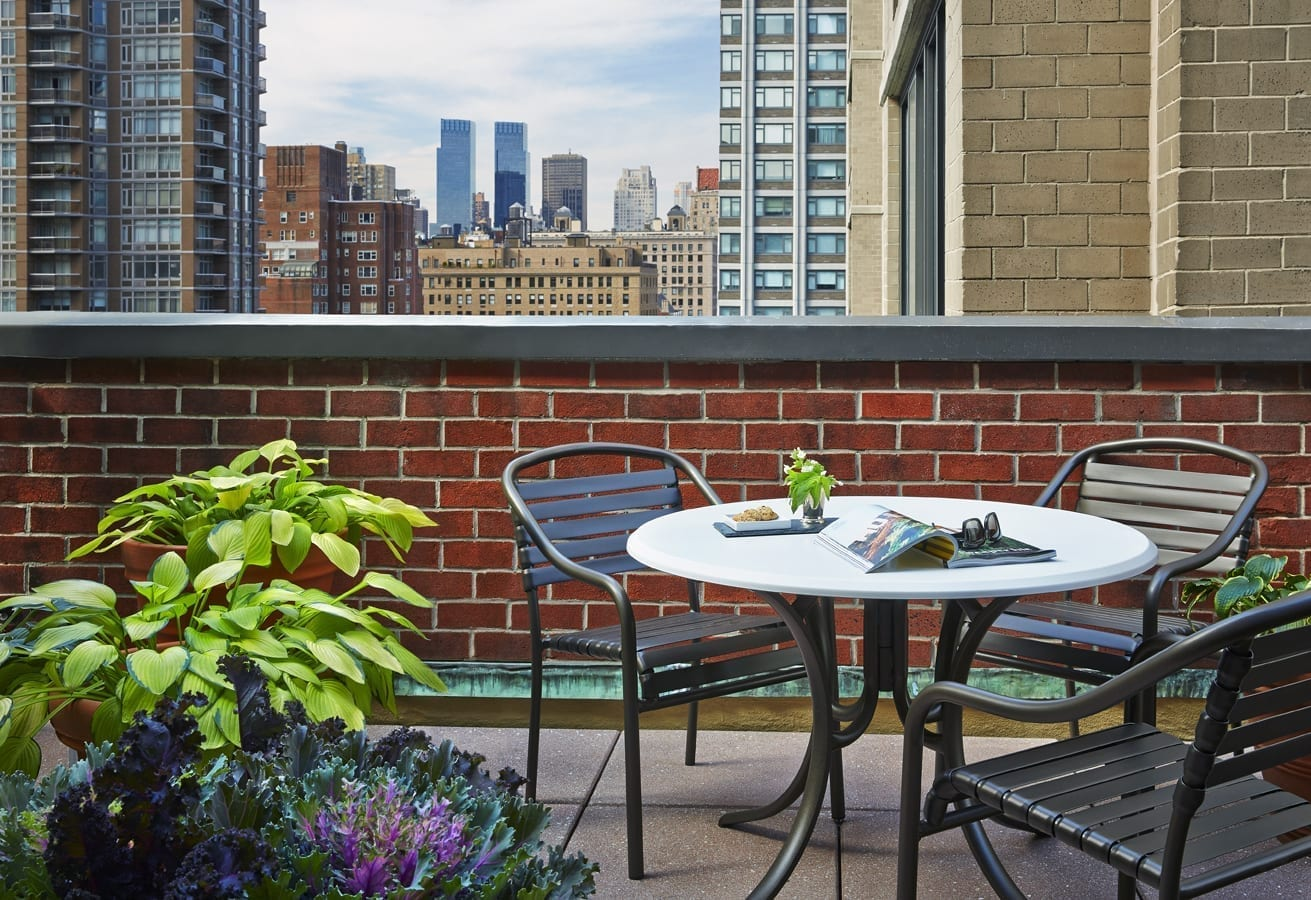 A round cafe table sits on one side of a Gardens Suites Hotel patio. A pair of potted plants is placed at one corner. On the table is small tray of snacks and small flower vase. A pair of sunglasses rest on an open magazine.
