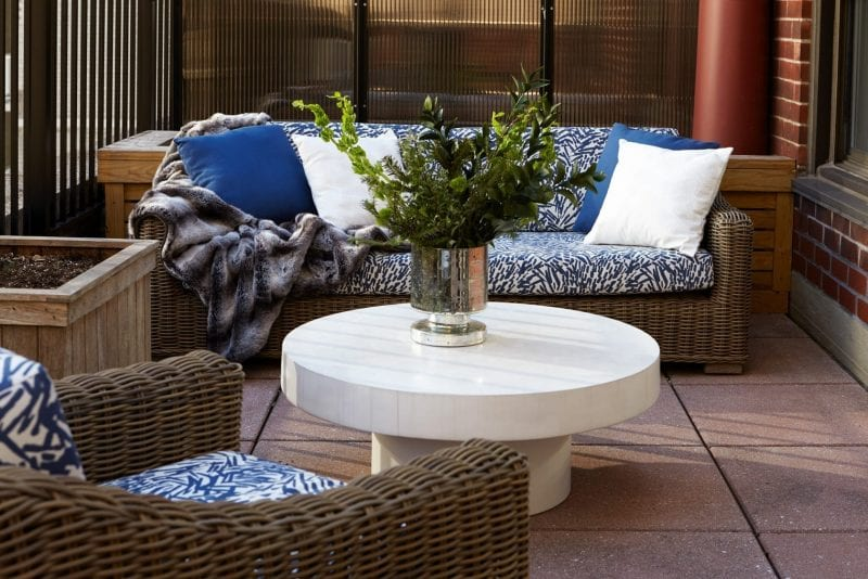 A couch and chair on the terrace of the Gardens Suite Hotel. A large round coffee table is placed at the middle, holding a flower vase. A fuzzy blanket has been thrown over one side of the couch.