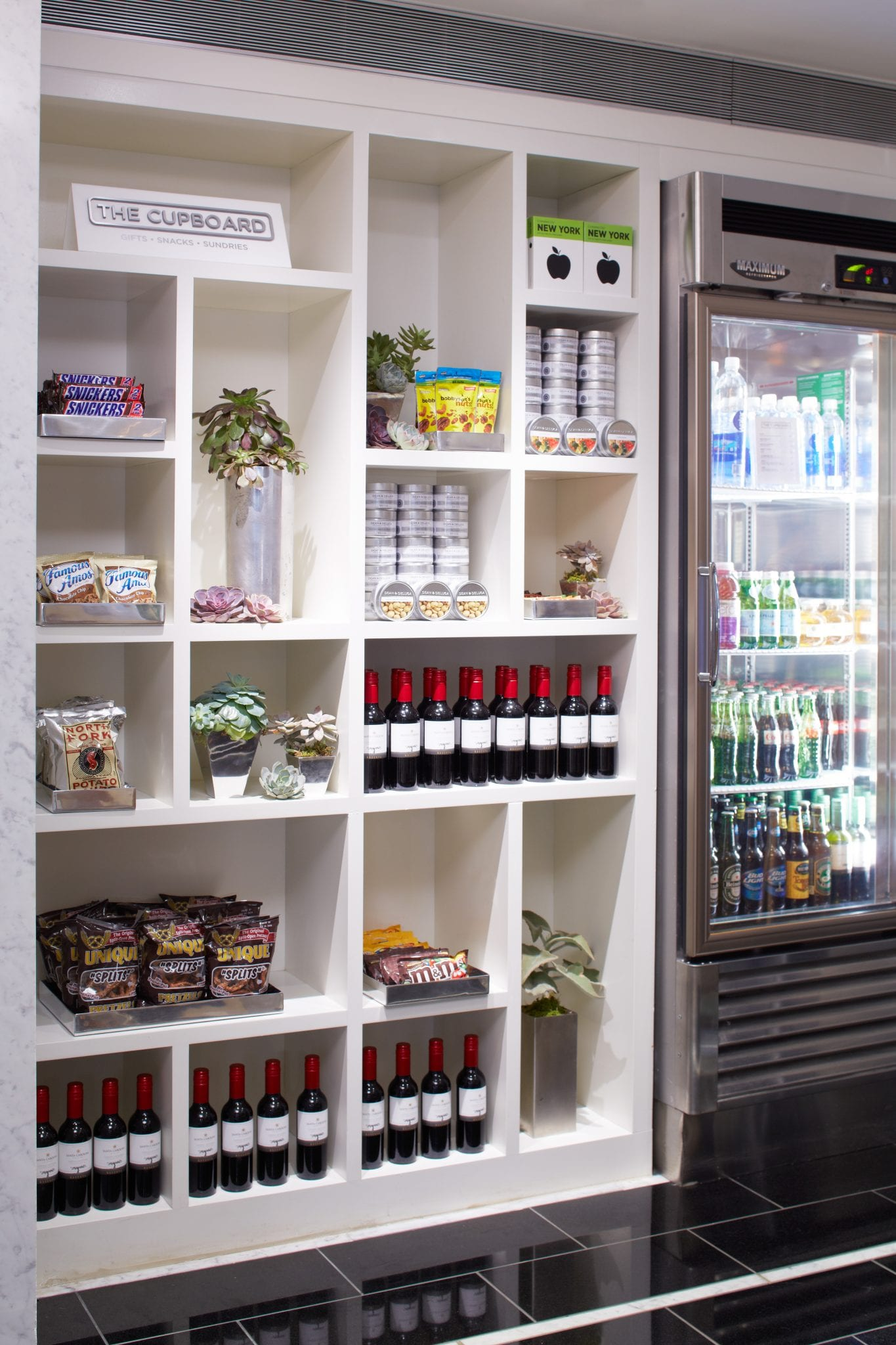Beverage refridgerator and shelves along the wall of The Cupboard of Affinia 50. Cookies and mixed nut snacks are well stocked along each shelf. A series of small wine bottles are placed on the bottom shelves, with another set on a middle shelf.