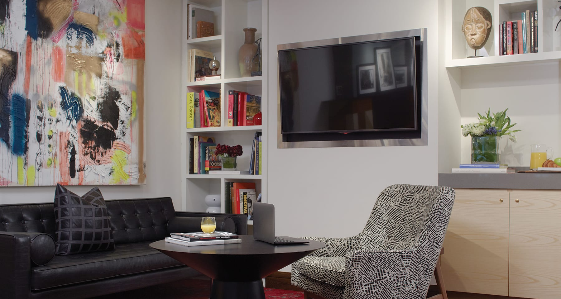 Corner of The Den, inside Fifty Hotel and Suites. White shelving holding books is to the left of a flatscreen television. A large painting hangs above the wide couch at the side.