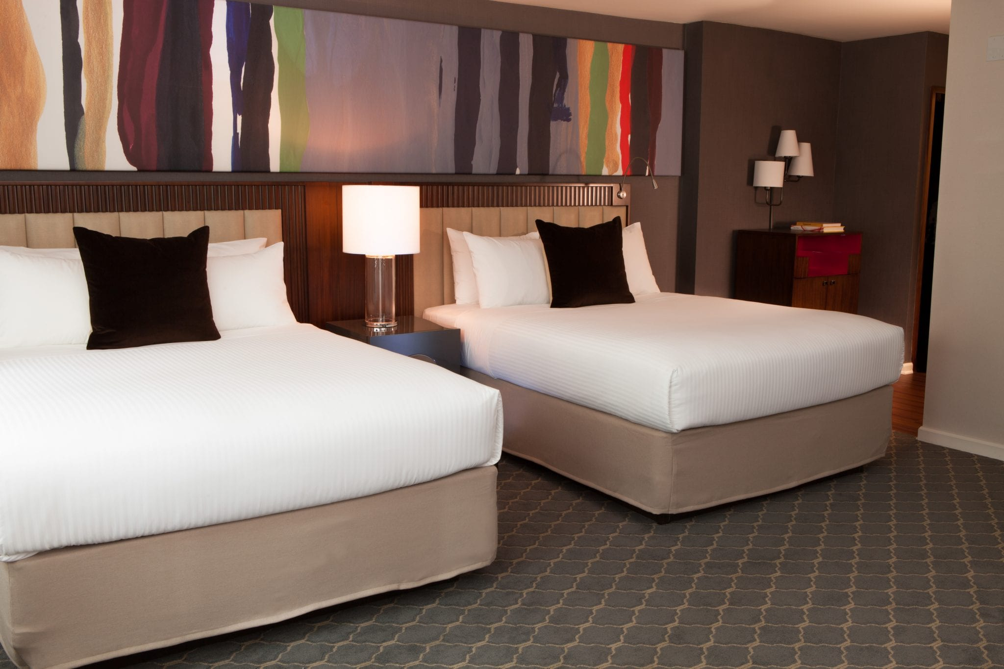 Two queen sized beds set up inside a Fifty Hotel guestroom. A nightstand is placed between the two beds. Above, an art canvas spans the length of these two beds.