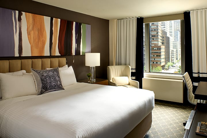 View of a king sized bed in the Fifty Hotel's One Bedroom suite. An abstract bit of art is hung over the headboard. The curtains are pulled open, allowing a view to the New York street.