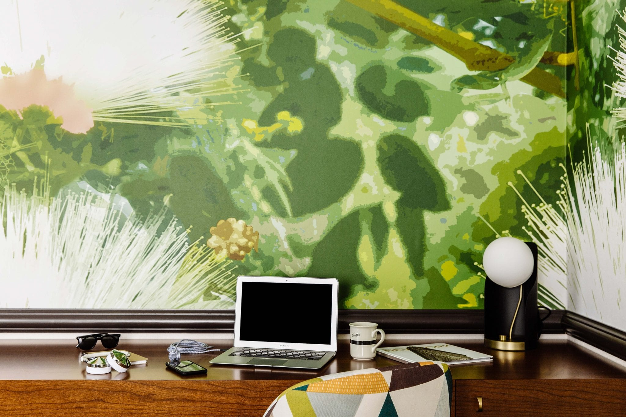 A desk setup for work inside Affinia Gardens Hotel suite. A laptop is set up, with a cup of coffee beside. A green mural is painted along the entire walls of this corner.