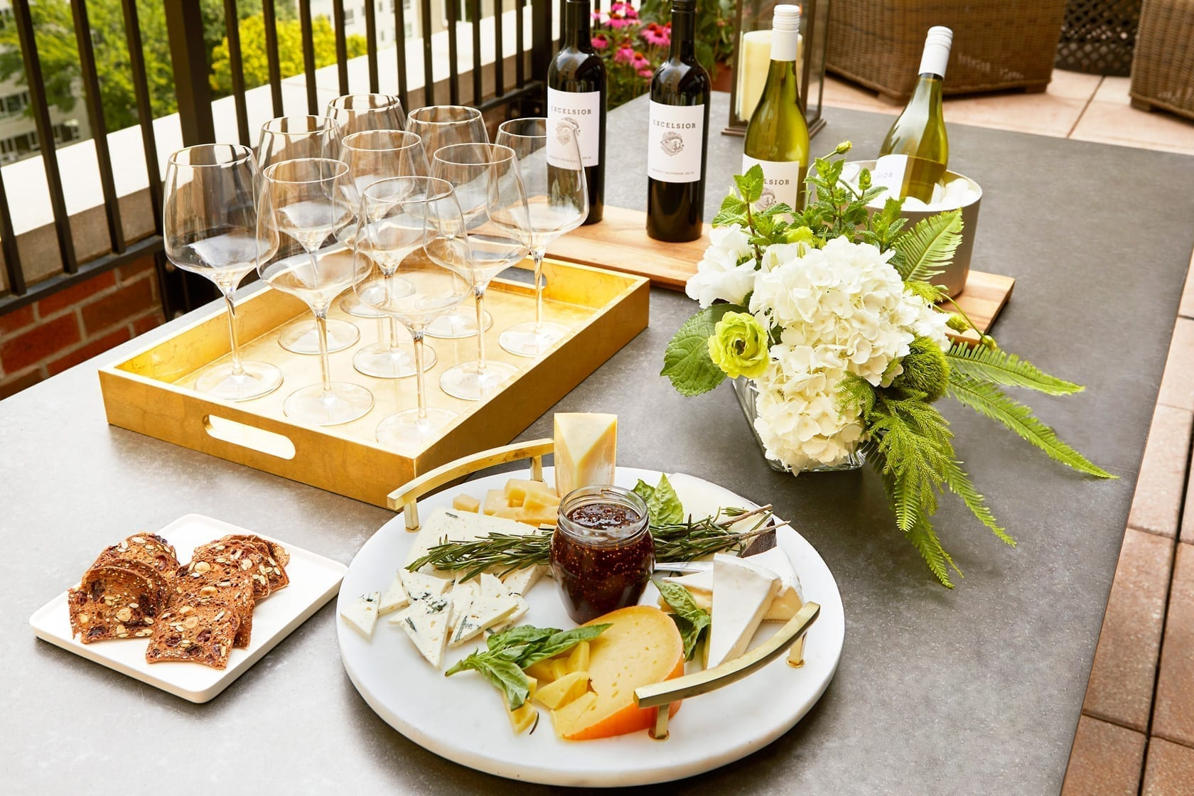 Table set for breakfast on one of Gardens Suites' terraces. A long thin board holds four bottles of wine, with one of them inside the metal ice bucket. A serving tray holds nine empty wine glasses. A large round tray holds a set of cheeses and the small square board off to the left holds bread.
