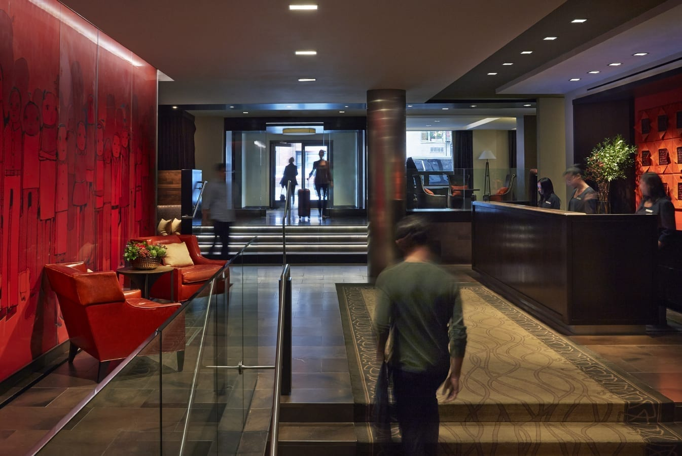 A man walks up the stairs leading to Shelburne Hotel and Suites' front desk. Across at the left are two red chairs against a red wall dressed with texture.