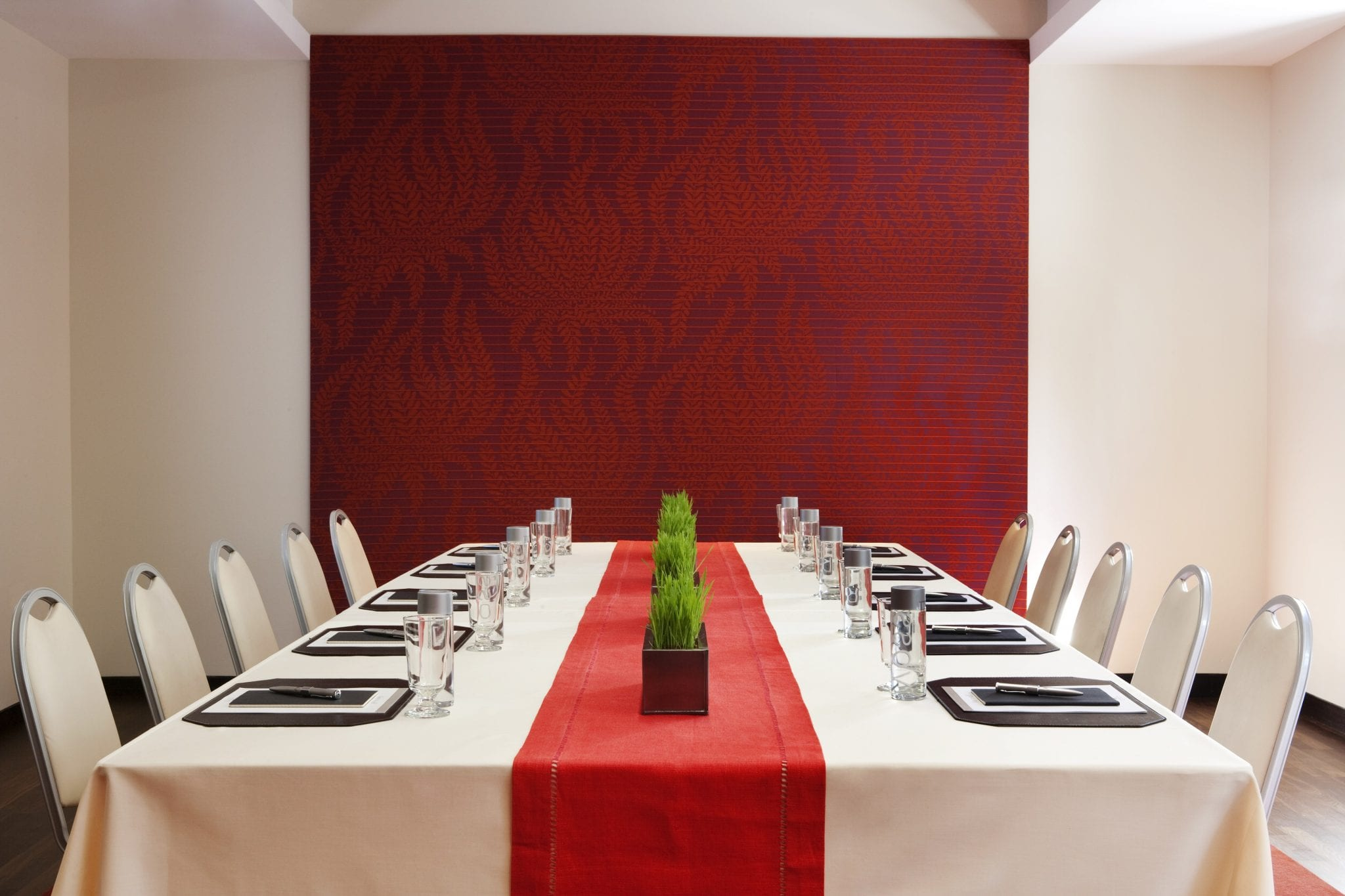 View from the head of a meeting table for ten people. A red table runner is placed atop the white table cloth, with small square planters placed down the middle.