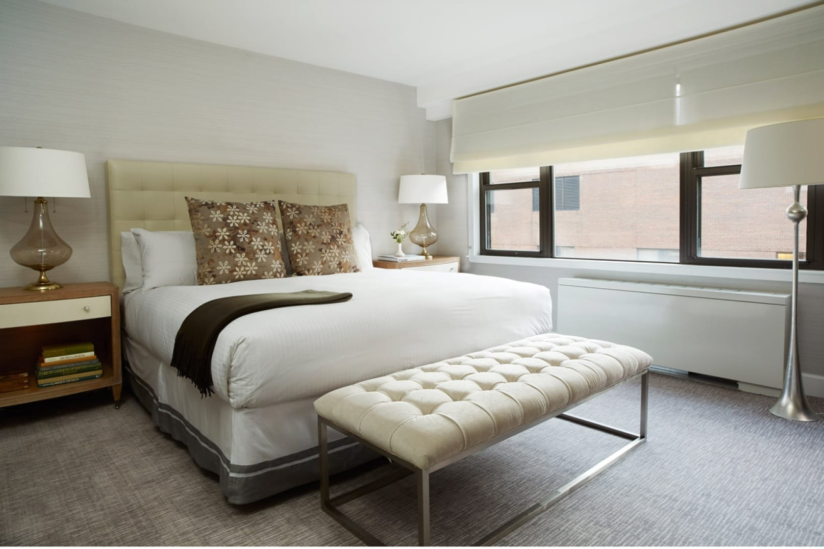 Perspective view of the king sized bed inside a Gardens Suites Hotel Penthouse. A cushioned bench with metal frame is placed at the foot of the bed. Two larger snowflake shape patterned pillows are placed in front of a stack of white ones.