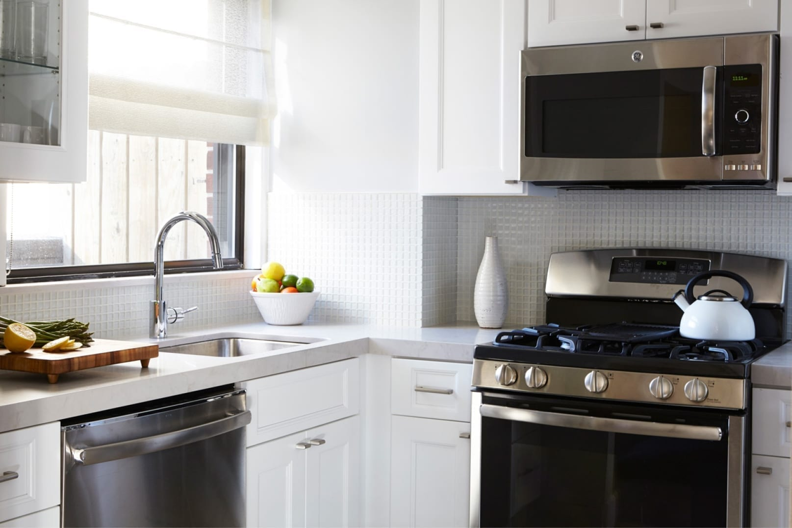 Corner of the kitchen, inside a Gardens Suite Penthouse. A white tea kettle is placed on the stove. A silver microwave above matches the stovetop. A bowl of fruit and a cutting board surround the window by the sink.