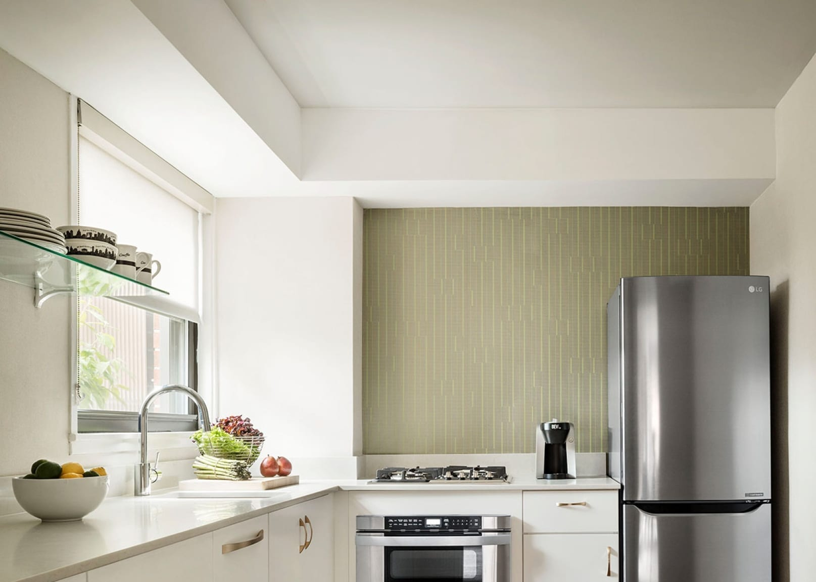 Looking into a kitchen of Affinia Gardens Suites. A window lets in light at the kitchen sink. An oven and tall silver fridge are placed against the side wall.