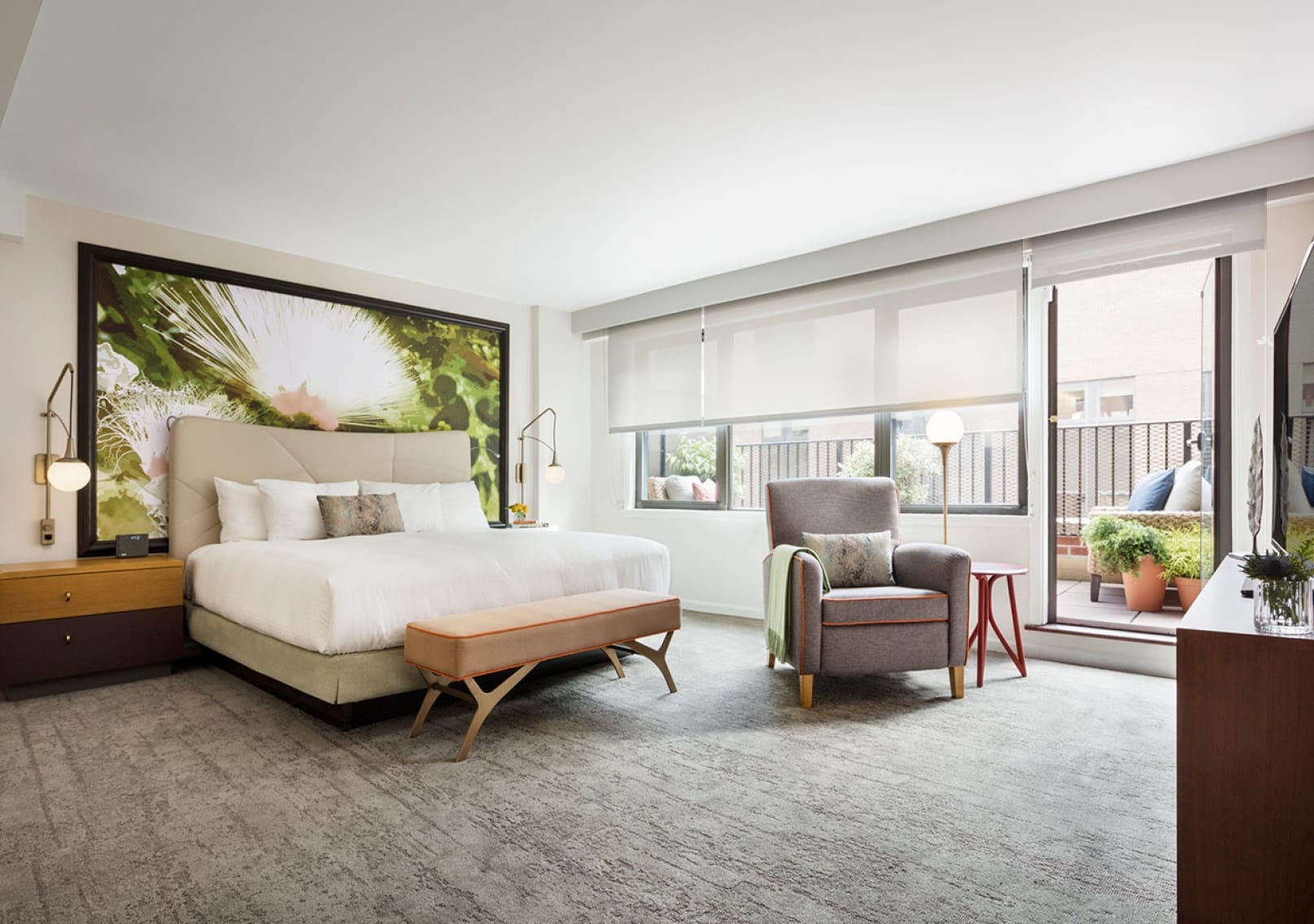 Perspective view of the large master bedroom inside Affinia Gardens' two bedroom suites. A large work of art spans the wall above a king sized bed. At the foot is a wooden bench. An easy chair is placed by the window, looking out to the terrace.