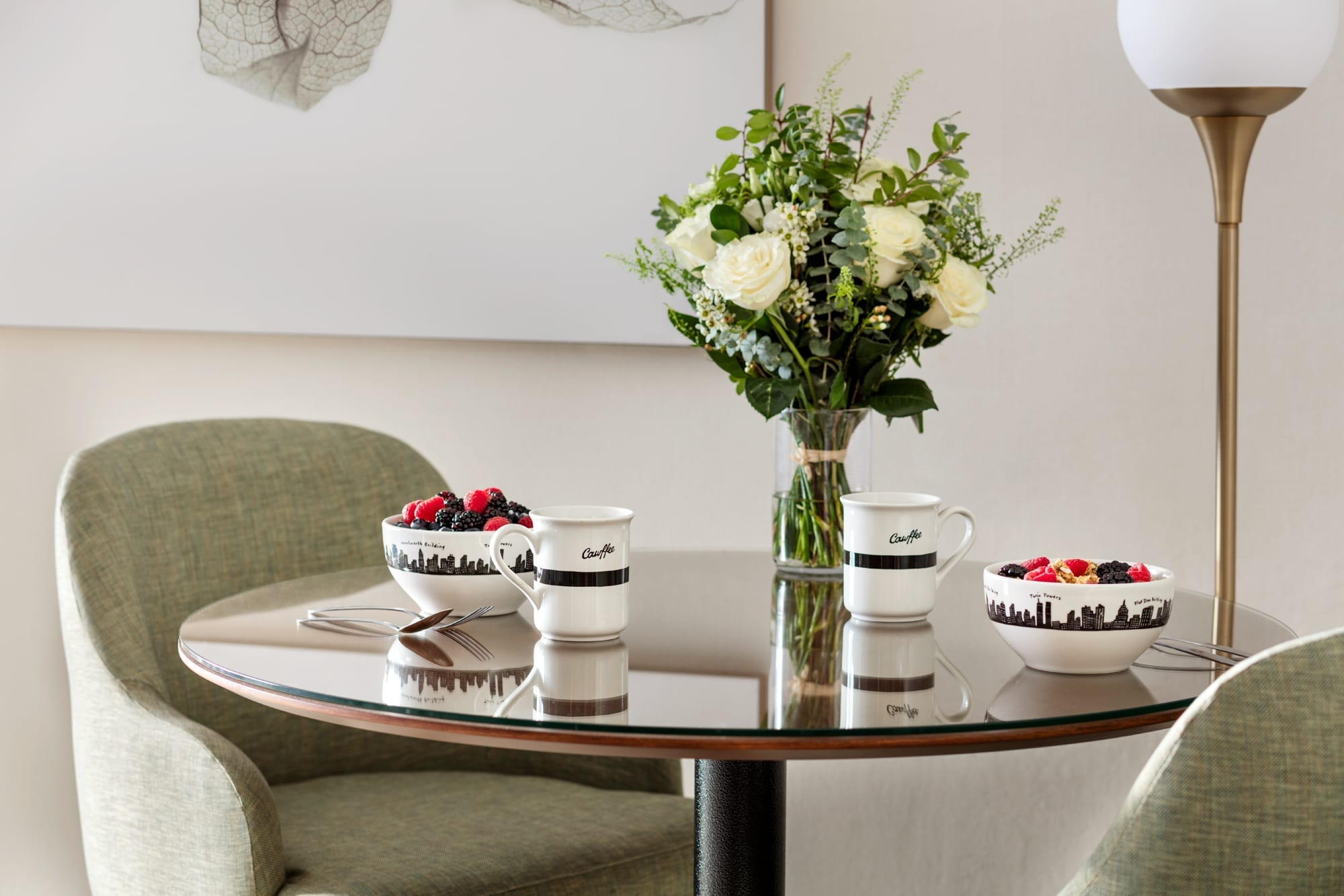Round dining room table set up inside the Affinia Gardens Junior Suites. A bowl of cereal is placed at each of the two settings. A glass flower vase rests off to one side.