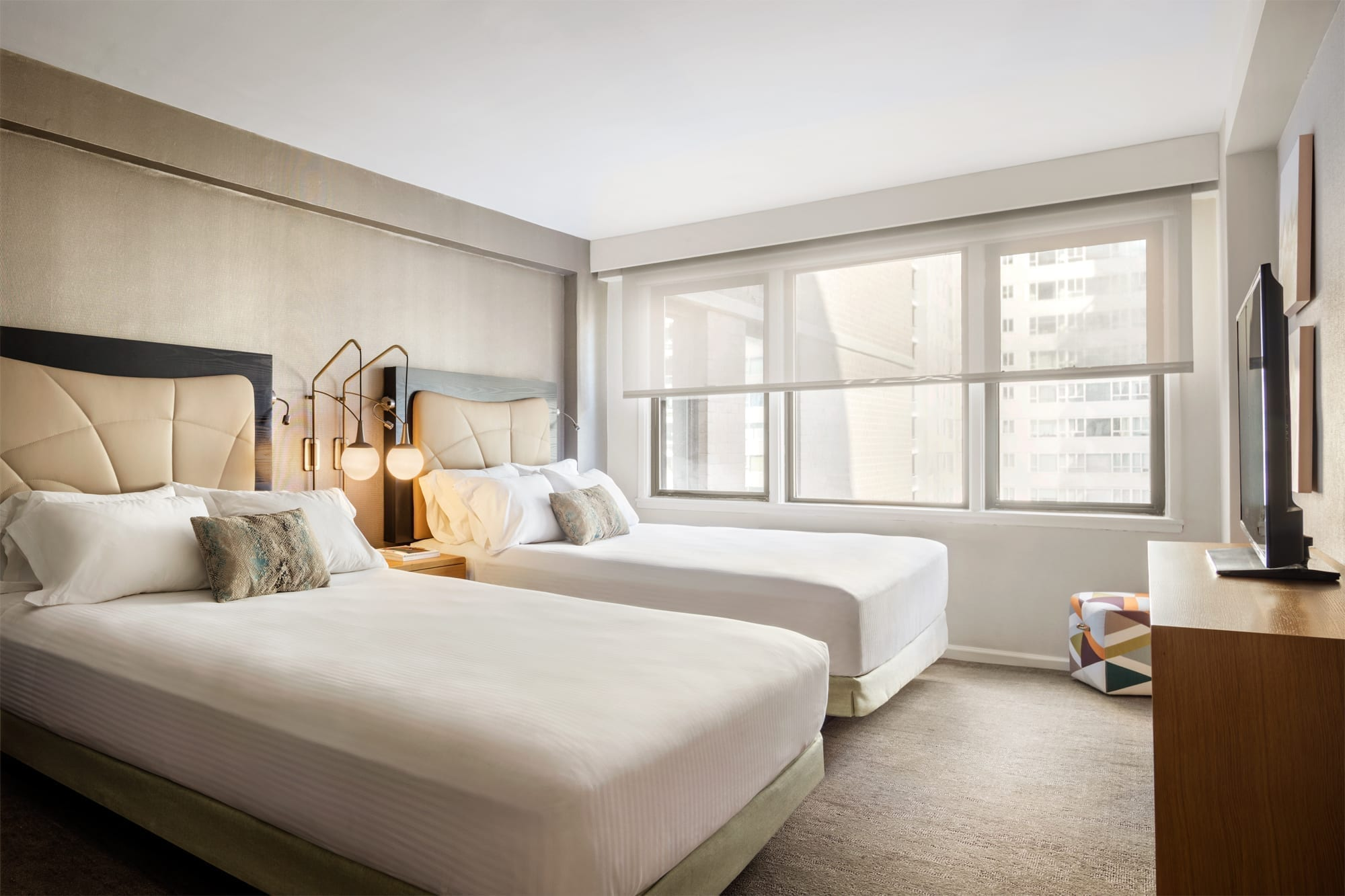 One of the bedrooms inside Affinia Gardens' One or Two Bedroom Suite. Two queen beds are placed against a wall, with a nightstand in between. The blinds are half drawn, bringing in light from the outside.