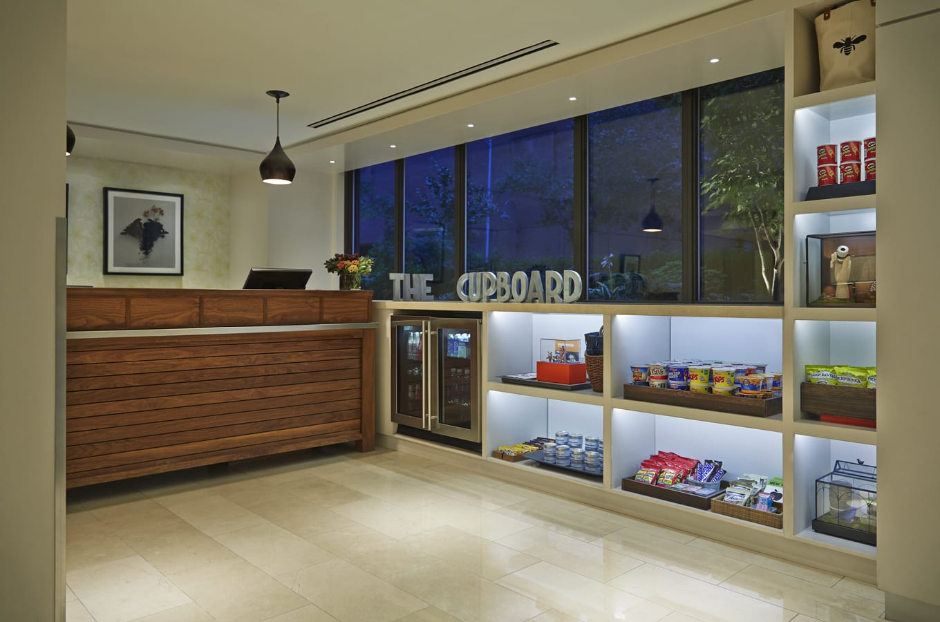 A view inside The Cupboard, a gift shop in Affinia Gardens Hotel. Various snacks and candies are placed on the shelves below and on the right. There is a set of decorative letters where the counter meets at the corner. It spells out