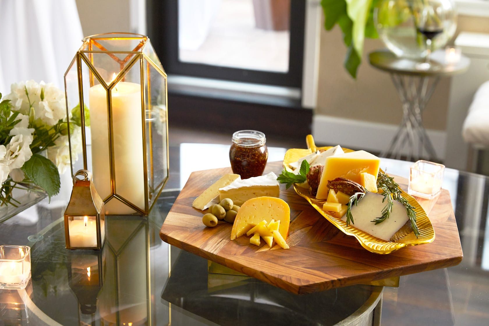 Close up of a wooden board, displaying meats and cheeses along a long plate. To the left is a glass of red wine and some cheese that is being sliced. A tall candle lantern is placed to the side of this display.