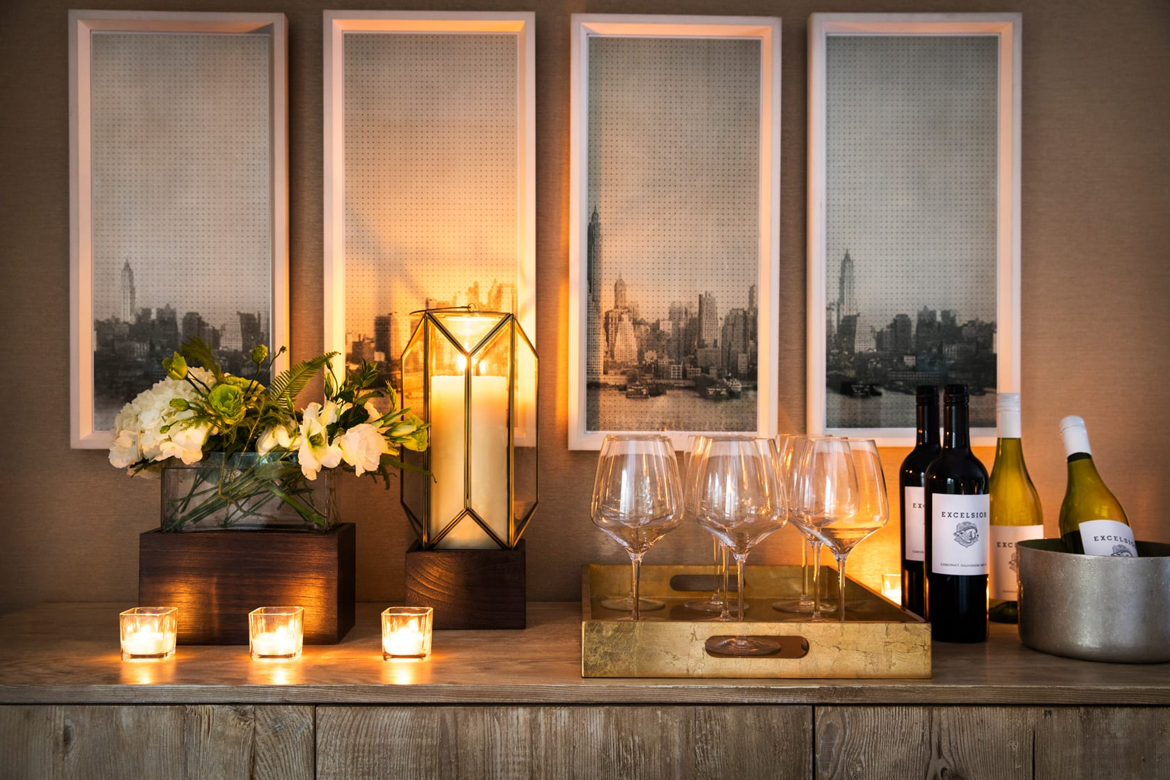 Wine bar setup inside a Gardens Hotel Penthouse Suite. At the far right is a metal ice bucket holding a white wine. A large gold serving tray holds nine empty wine glasses. Two red wine bottles and another white wine bottle are just beside it. Three votive candles are placed to the left, with a taller candle and flower vase behind.