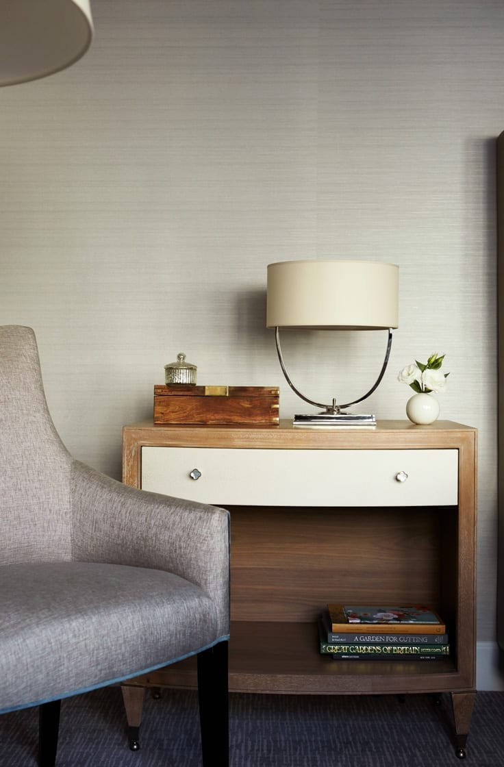 Nightstand inside the Gardens Suites Hotel guestroom. A metal lamp base is dressed with a white oval lampshade. A small wooden box is closed, with a small jar placed on top.