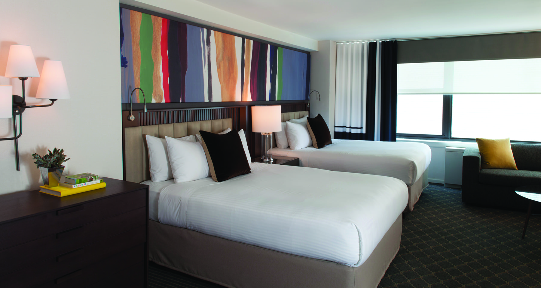 Perspective view of two queen beds inside the Junior Suite of Fifty Hotel. A wide canvas of artwork is hung above.