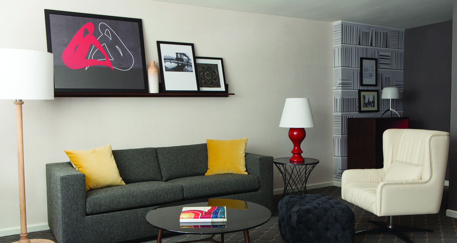 Couch and chair of Fifty Hotel's One Bedroom Suite. A book rests on the round coffee table in front. Framed artwork and photos are placed on a mantle above.