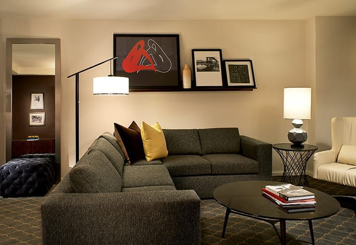 View into a living area of a Fifty Hotel and Suites accommodation. An L-shaped couch is placed on one side, the mantle above holding three framed pictures. A stack of books is on top of the round coffee table.