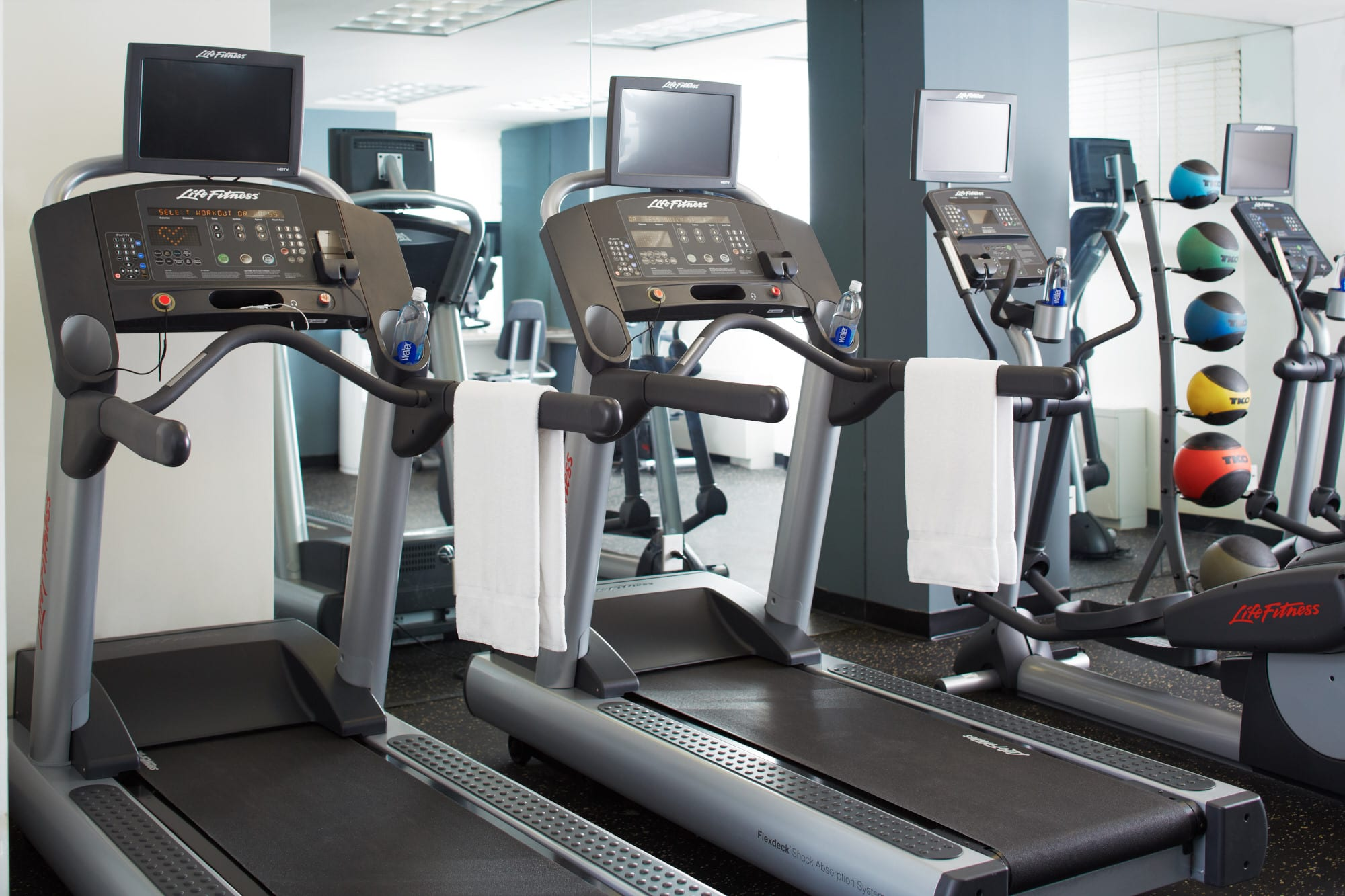 Row of treadmills and a pair of elliptical machines inside Fifty Hotel's fitness center.