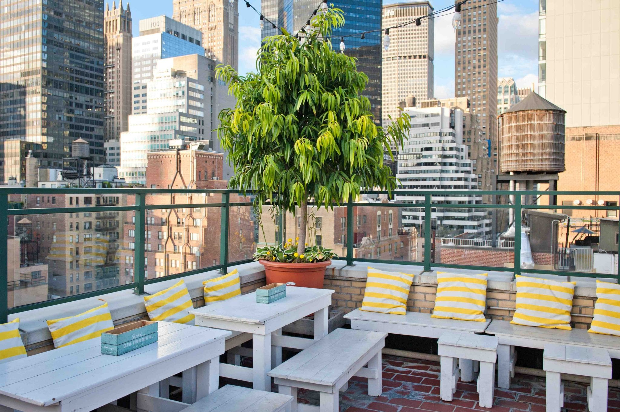 Perspective view of the New York City Skyline from the Rare View Rooftop. Wooden white benches and tables are place all along this corner.