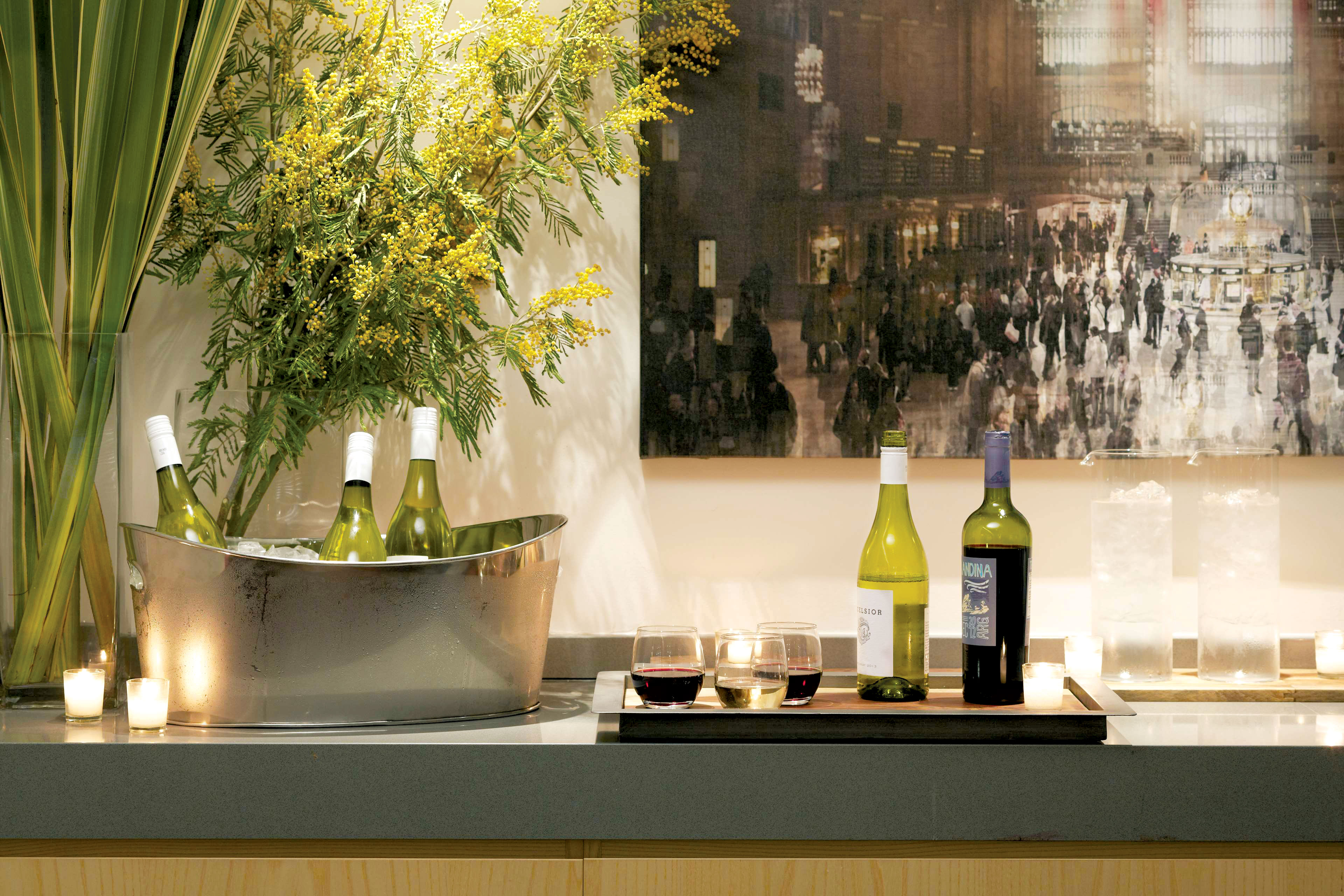 Wine Glasses And Wine Bottles On A Counter Top In The Den At Fifty Hotel & Suites